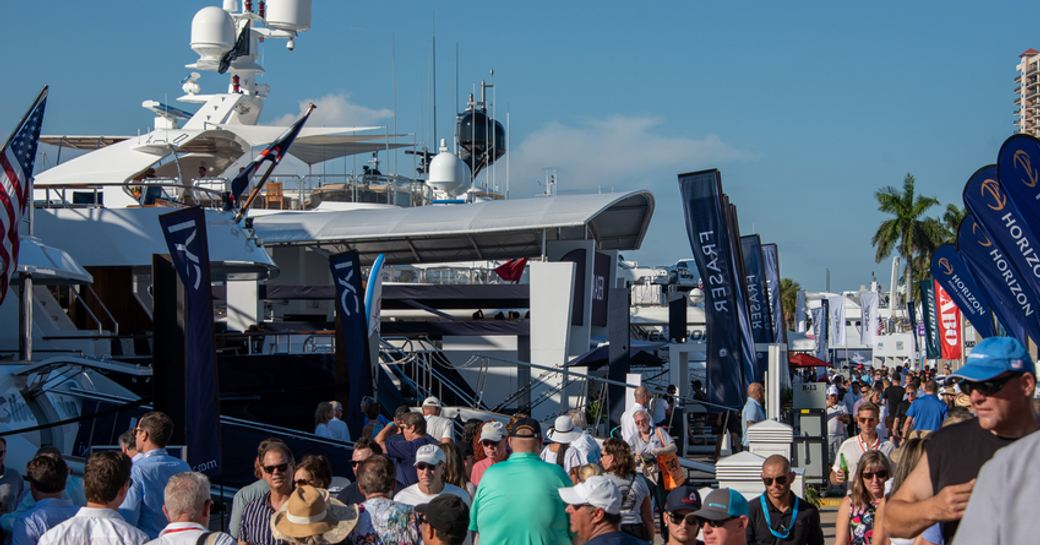 Glimpse of some exhibitors at FLIBS, yachts moored on either side of floating dock with hundreds of visitors walking in between.