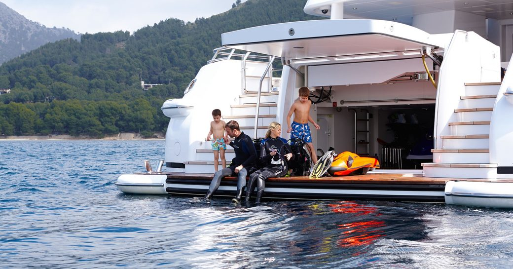 charter yacht spirit, with charter guests enjoying some scuba diving off the swim platform