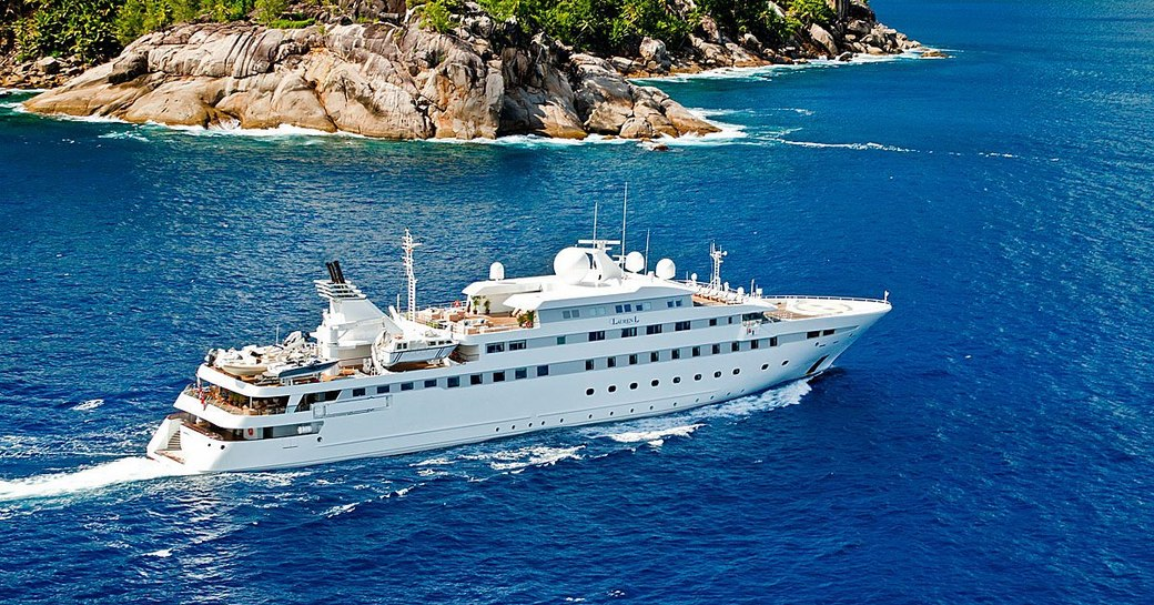 Superyacht 'Lauren L' cruising near to a green coast