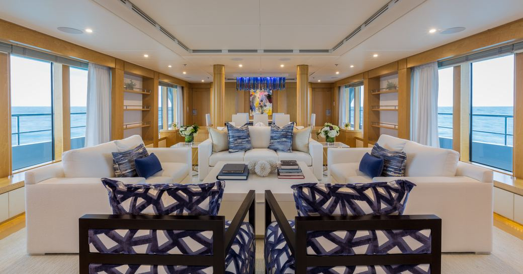 Light and airy open salon on Superyacht BACA with comfortable sofa and glass windows down either side