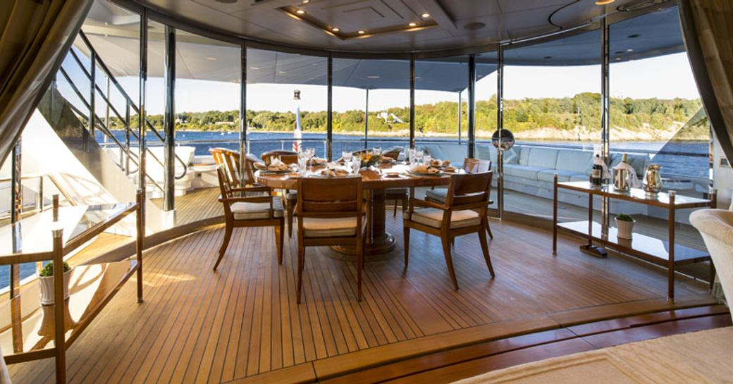 dining area on bridge deck aft with removable full-length glass panels aboard superyacht 'Blue Moon'