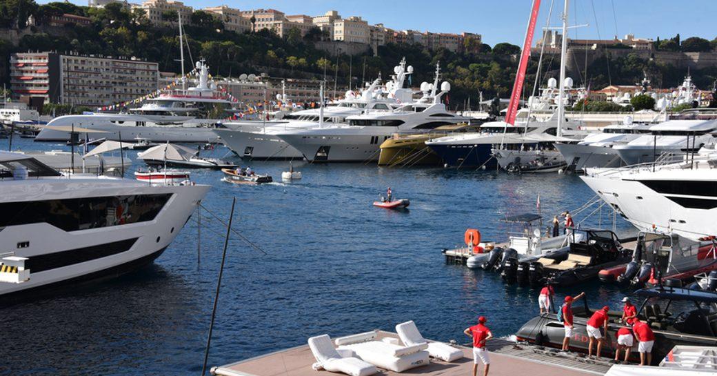 Superyachts moored, with tenders travelling between through Port Hercule, Monaco. Crew onboard nearest yacht awaiting visitors.