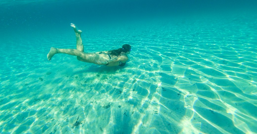 Woman on private yacht charter snorkels in clear blue sea in Ibiza