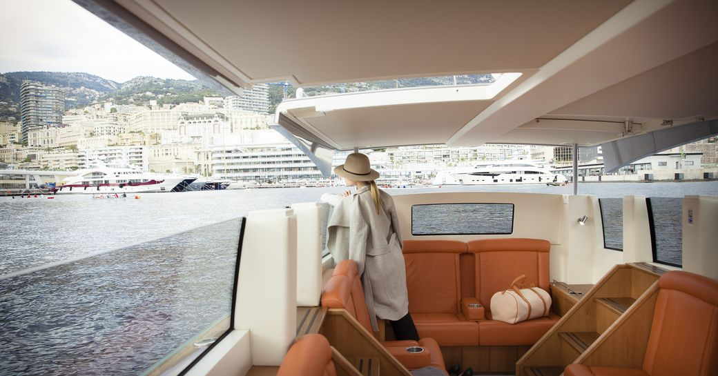 A charter guest surveys a harbor from the comfort of a limousine tender