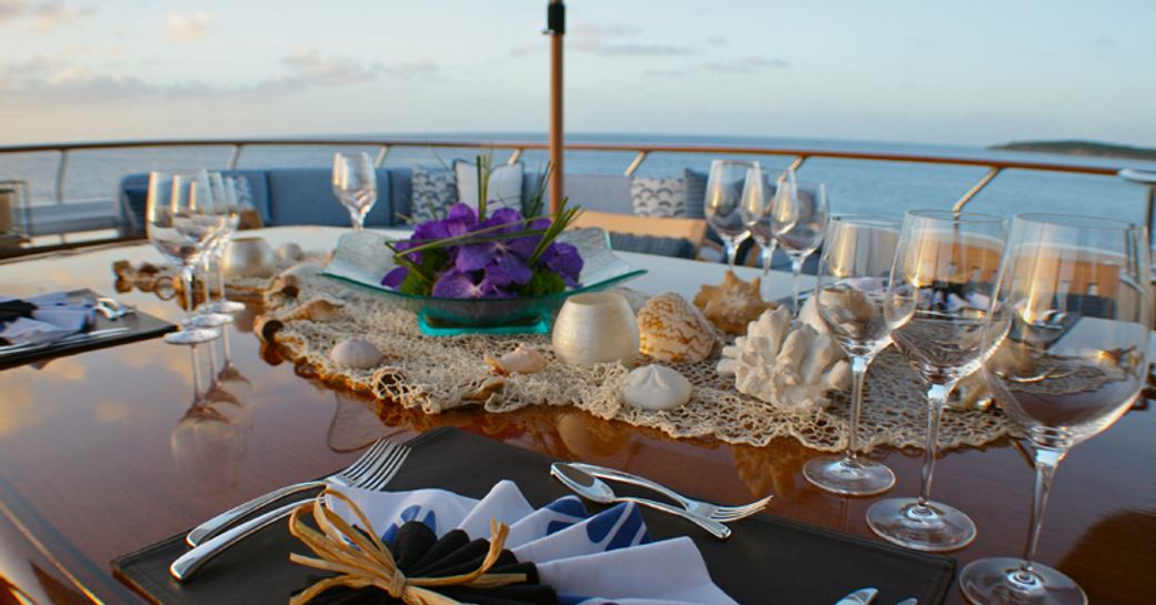 the alfresco dining are on the main deck aft of charter yacht Lady J as the sun sets romantically behind