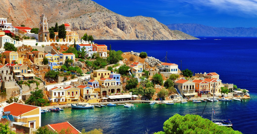 island of symi in greece, coloured buildings and sapphire water, mountain backdrop