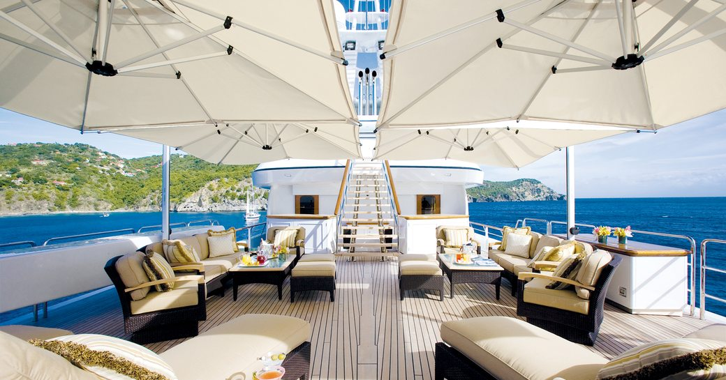 Sundeck on superyacht SOLO with alfresco seating areas and parasols