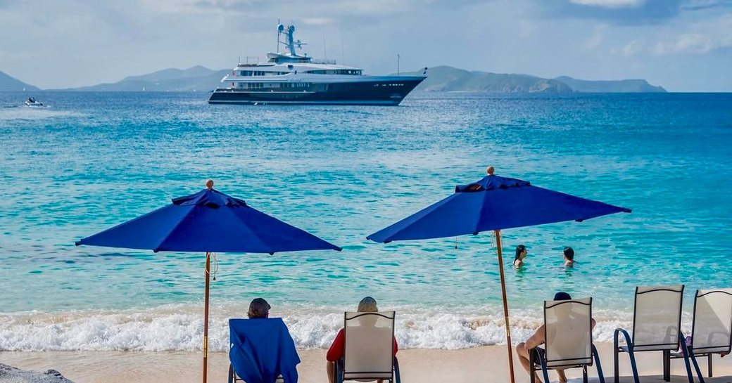 family sit on sandy beach looking at yacht on the horizon during yacht charter vacation in the bahamas