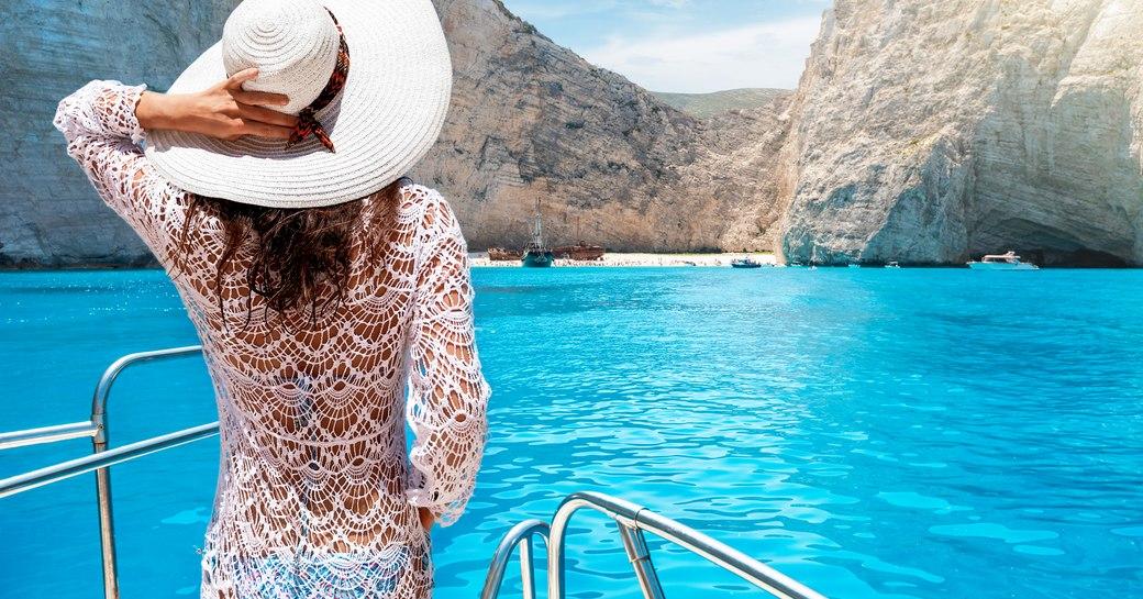 Woman on bow of yacht nears Shipwreck beach in Zakynthos, Greece
