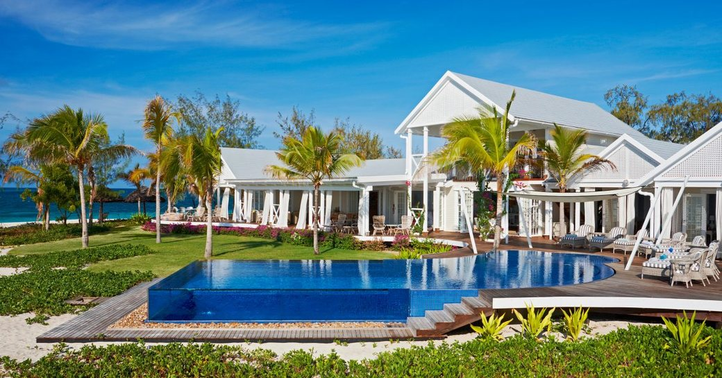 Private island, Thanda Island, shot of villa accommodation and glass-edged infinity pool with palm trees in background and terrace seating around pool