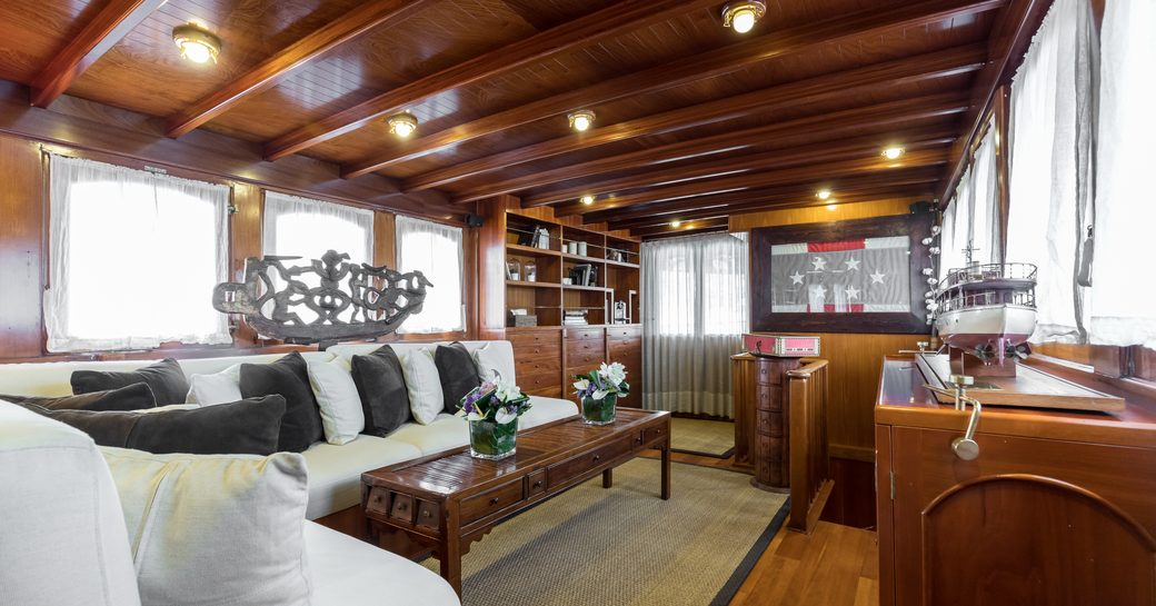 classic motor yacht over the rainbow main salon with polished wood surfaces, white sofas and flag framed on wall