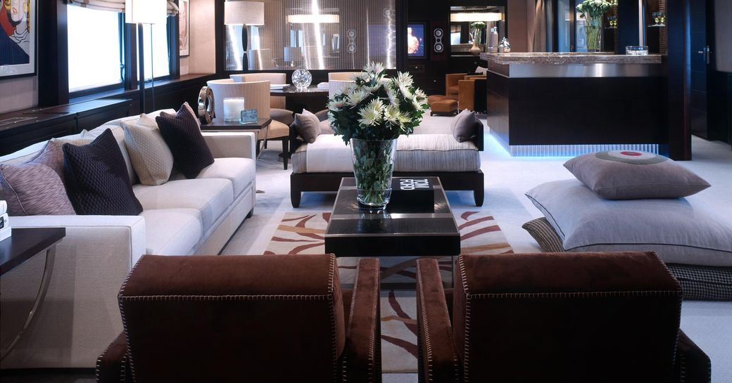 Interior of Illusion I yacht - showing sofas and table with flowers on