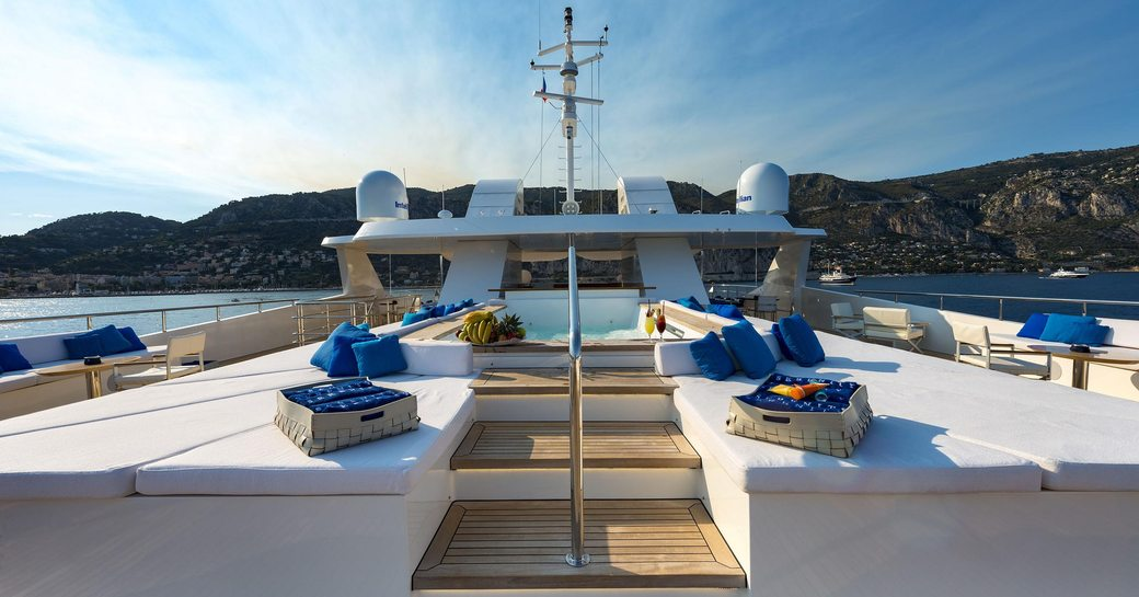 Overview of sun deck onboard M/Y SERENITY, central pool with sun pads in foreground, overlooking elevated terrain in background