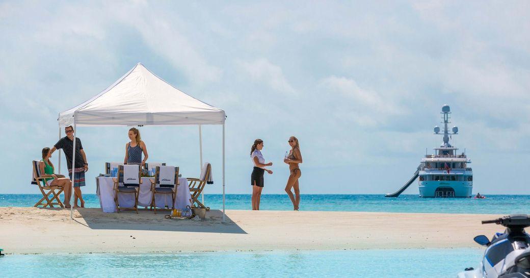 luxury yacht and beach picnic, with beach picnic on sand bar