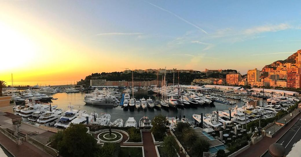 A collection of superyachts photographed at sunset during the Monaco Yacht Show