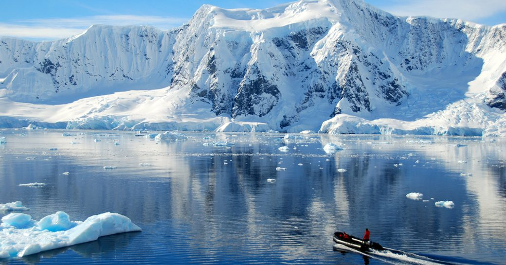 RIB tender explores the calm waters and dramatic snowy landscapes of Antarctica