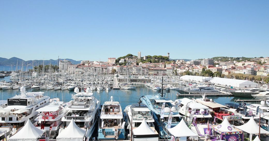 Marina at Cannes with all berths filled with motoryachts and sailing boats, Cannes settlement in background