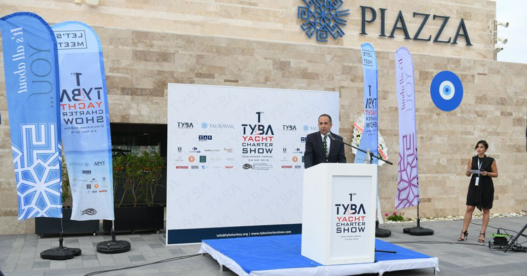 Speaker on stage during TYBA event, surrounded by flags.
