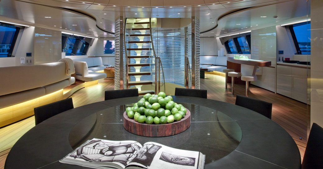 main salon on luxury sailing yacht panthalassa, with black table in foreground and staircase in background