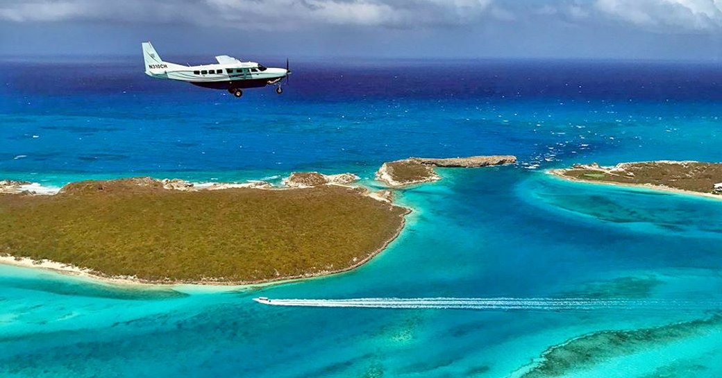 private chartered plane flying across the blue sea and islands of the exumas