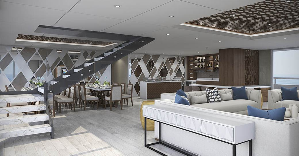 white sofas with bar and dining area beyond in the main salon aboard luxury yacht ELITE