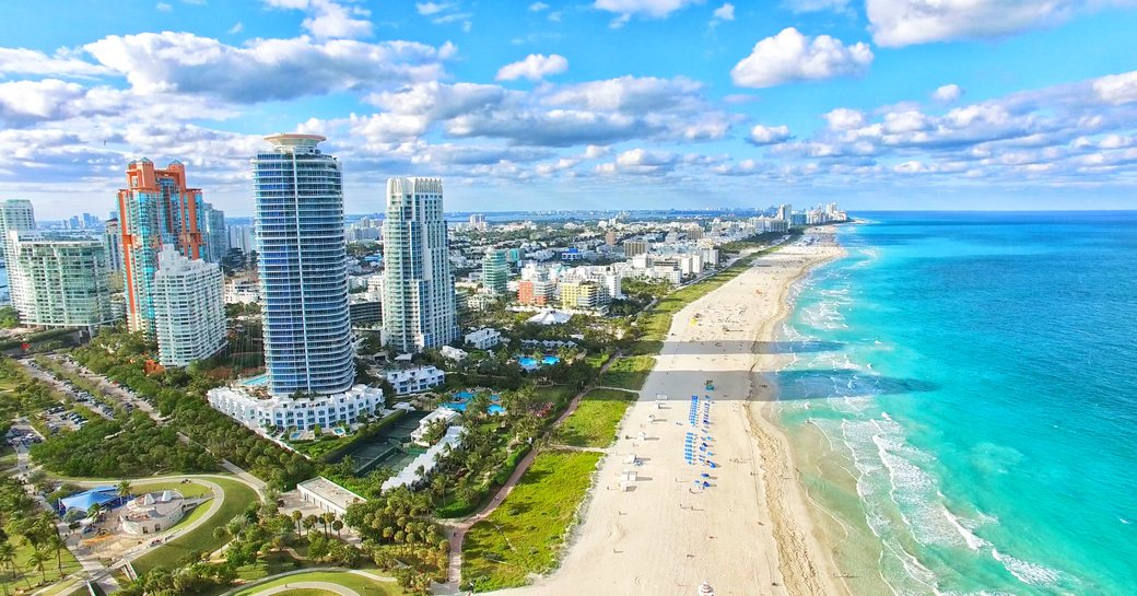 Overview of South Beach, Florida. Sandy beach adjacent to towering hotels and teal sea.