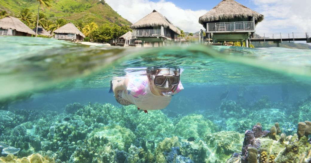 underwater view of girl snorkeling in the maldives
