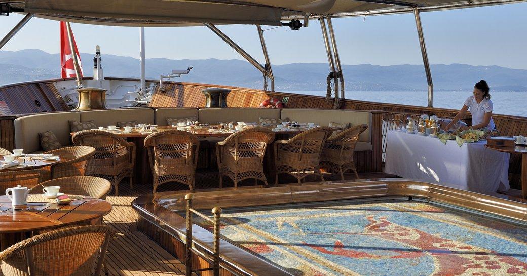 Alfresco area with mosaic pool on megayacht Christina O, with alfresco dining set-up