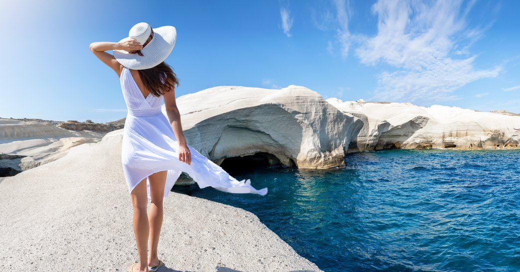 Woman stands on Sarakiniko Beach, looking out over the sea and the island of Milos