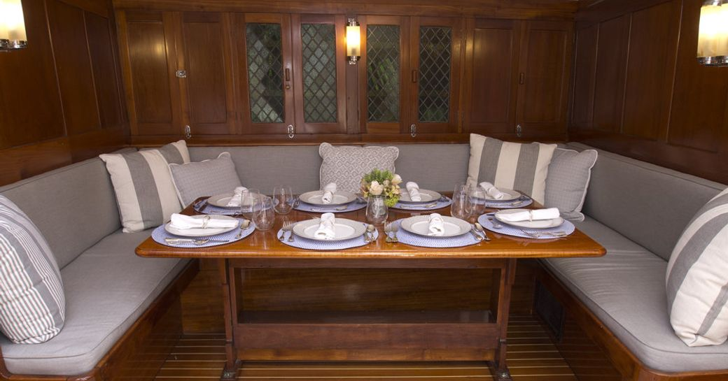 U-shaped seating and dining table in the interior of luxury yacht EROS