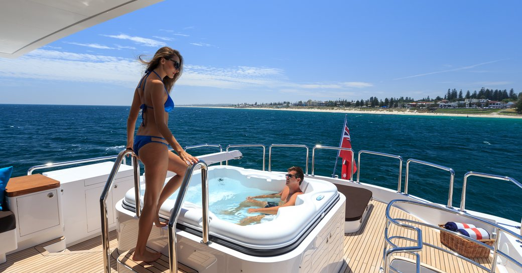 Charter guests enjoy the Jacuzzi on upper deck of motor yacht Paradise