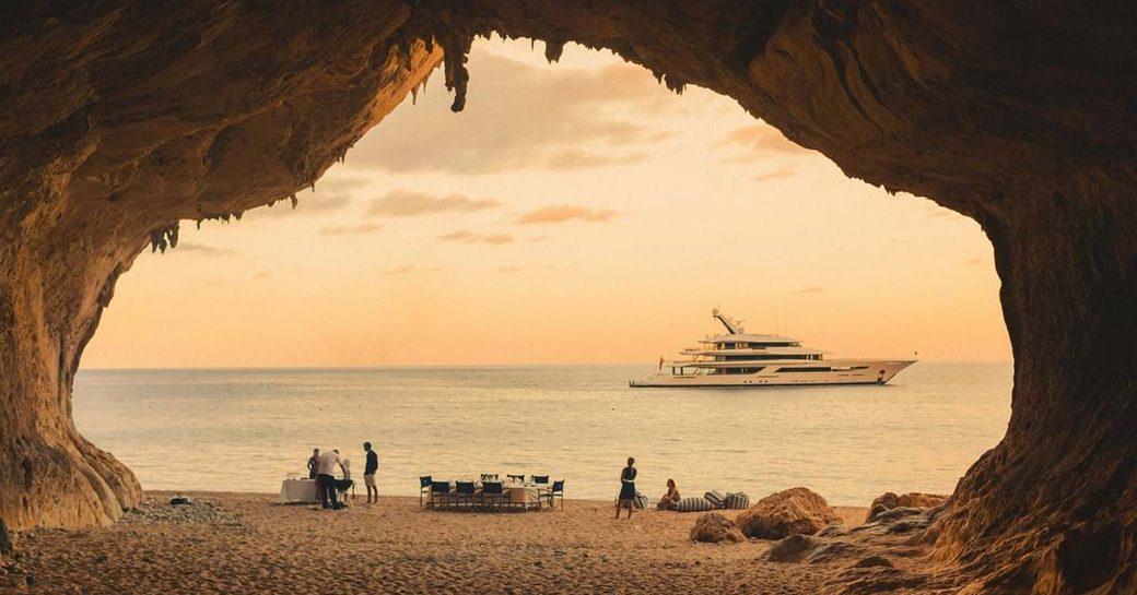 joy superyacht by feadship in water overlooking sardinian sandy beach of cala luna