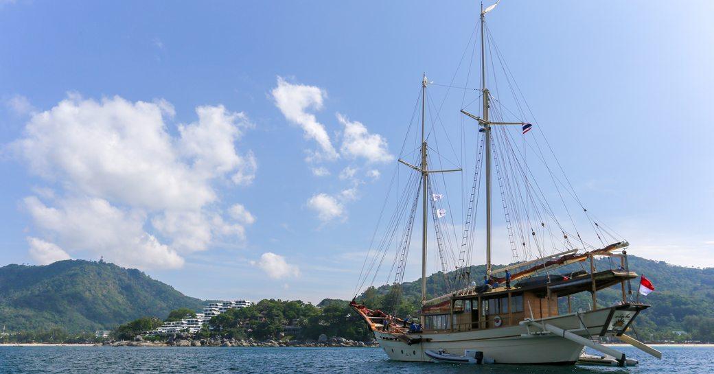 Charter yacht LAMIMA at-anchor outside the Kata Rocks resort