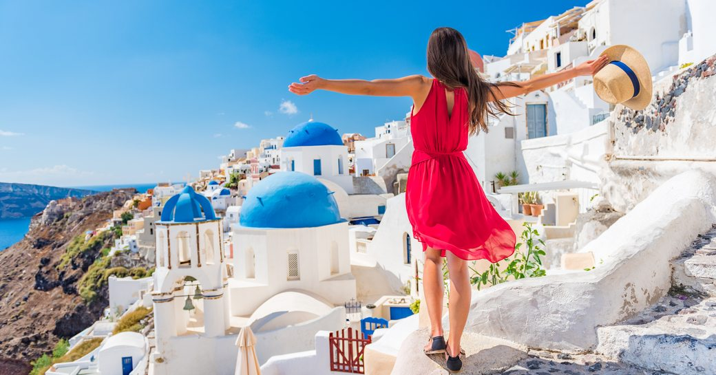 A woman in red stands on a hilltop village in Santorini, Greece