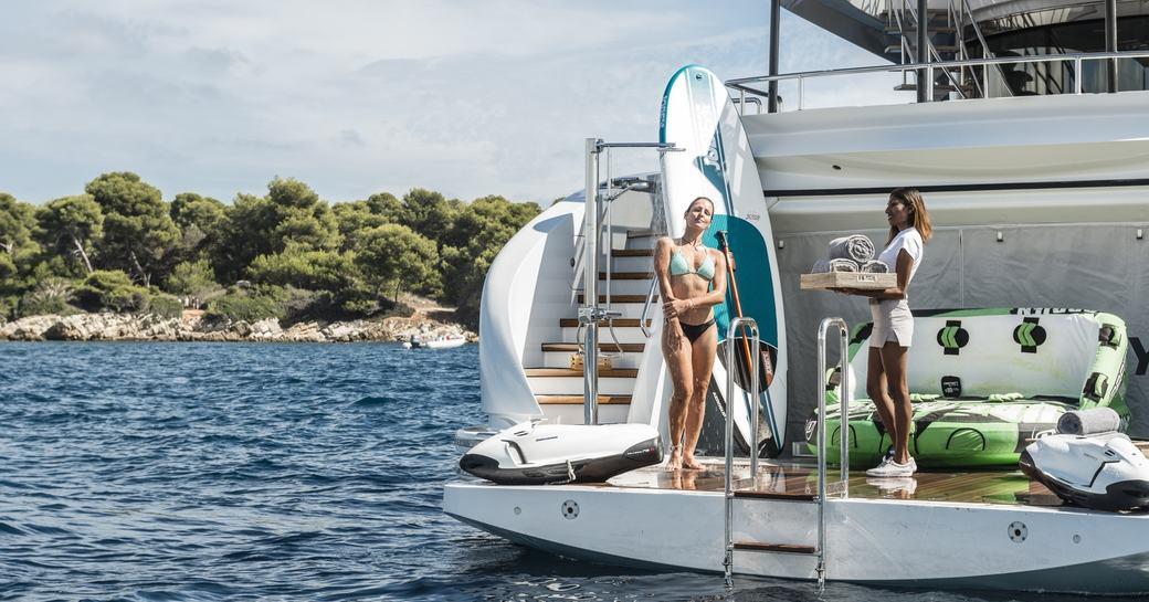 guests on yacht charter enjoy swim platform in greece