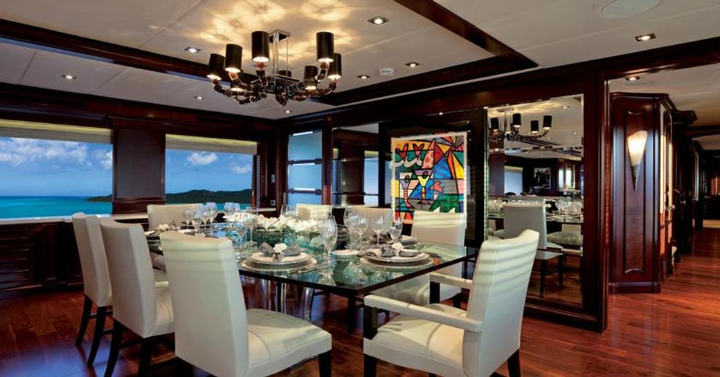 formal dining indoors on charter yacht alessandra, with chandelier above and contemporary art on wall in background, plenty of glass laid out on table
