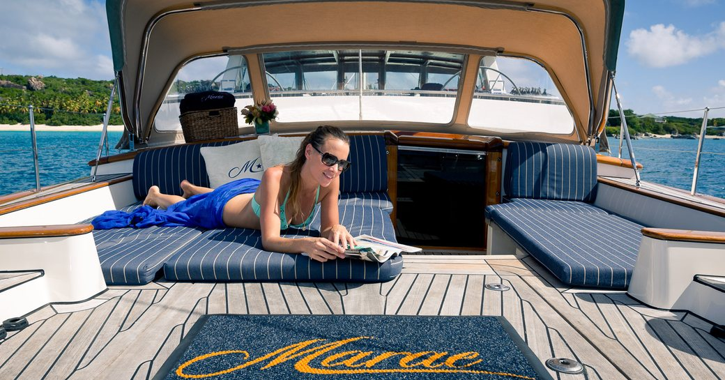 Guest enjoys a book whilst on her luxury charter vacation