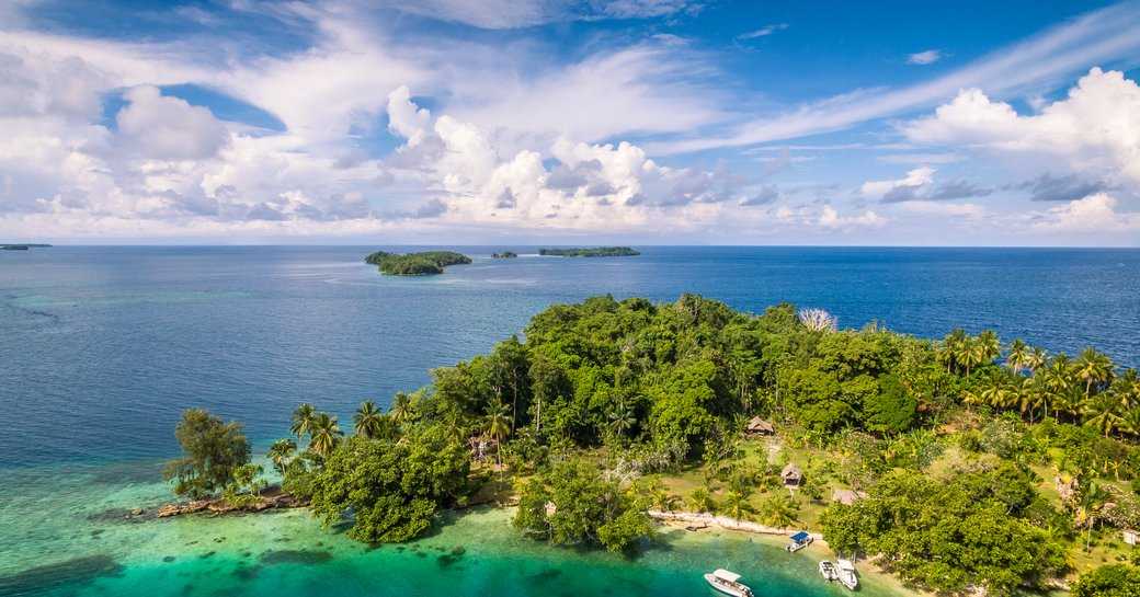 isand in papua new guinea covered in jungles with turquoise ocean surrounding