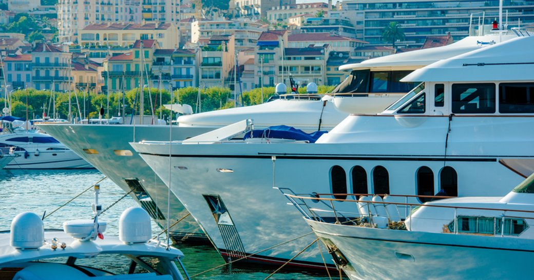 Line of motor yachts moored at Cannes Yachting Festival, Cannes visible in background past bows of yachts.