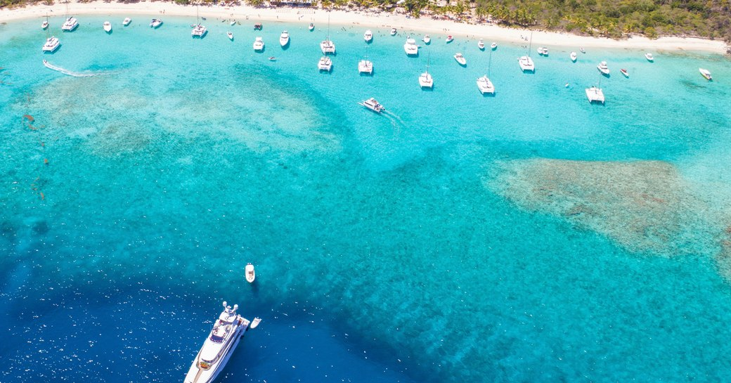 a superyacht cruising the multi hued tropical blue water of the virgin islands