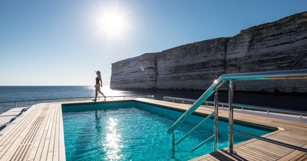 Pool on deck of Superyacht LANA with lady in swimsuit and coast in background