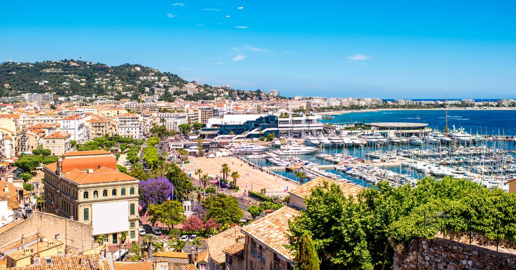 Elevated view of Cannes, buildings in foreground with marina down below. Many yachts berthed.