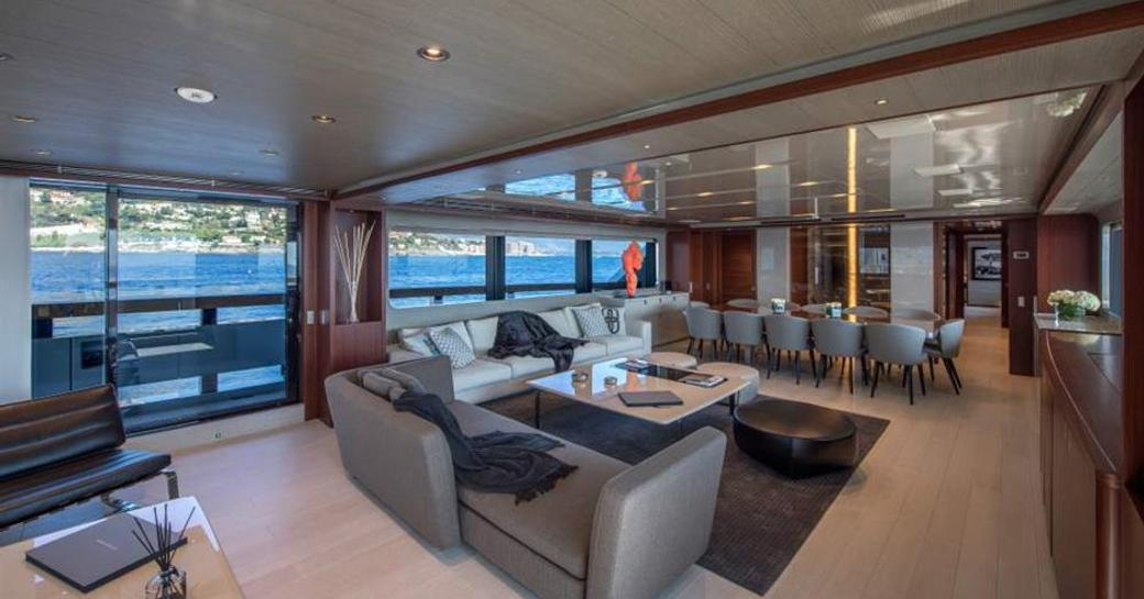 luxury yacht x main salon with sofa seating and dining table