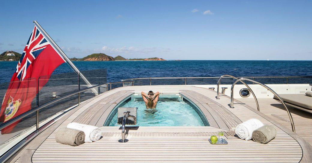 A guest relaxes in the Jacuzzi on board superyacht Grace E
