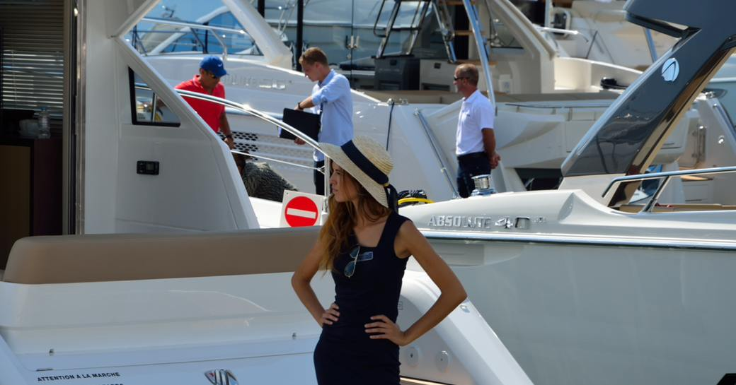 Woman stands on deck of yacht at cannes yachting festival