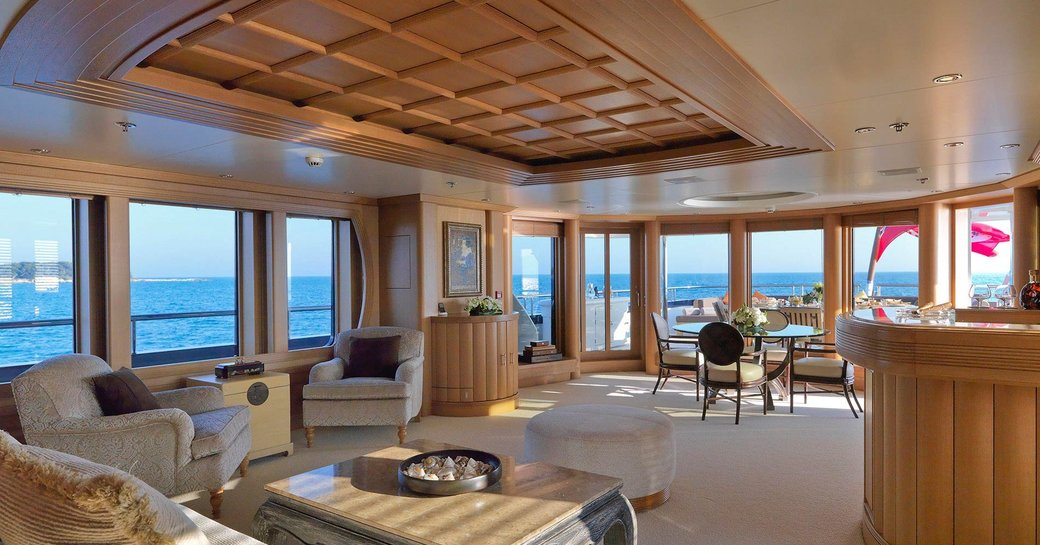 skylounge with bar, seating and large windows on board motor yacht Deja Too