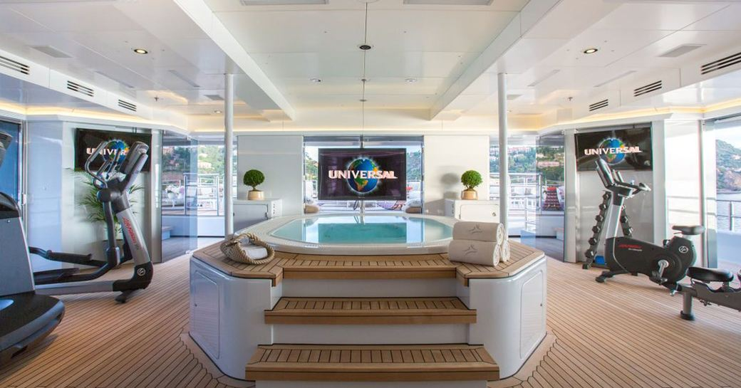 pool on deck of luxury yacht naia, with tv screen and gym equipment