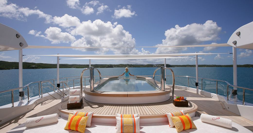 A charter guest stands by the pool on board superyacht AMARYLLIS