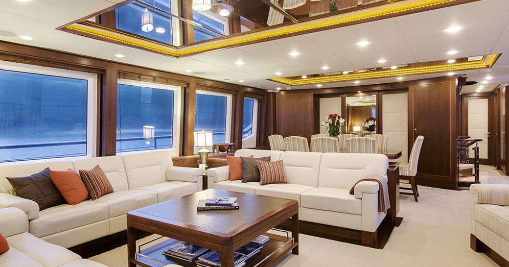 sociable lounge with dining table beyond in main salon of motor yacht Masteka 2