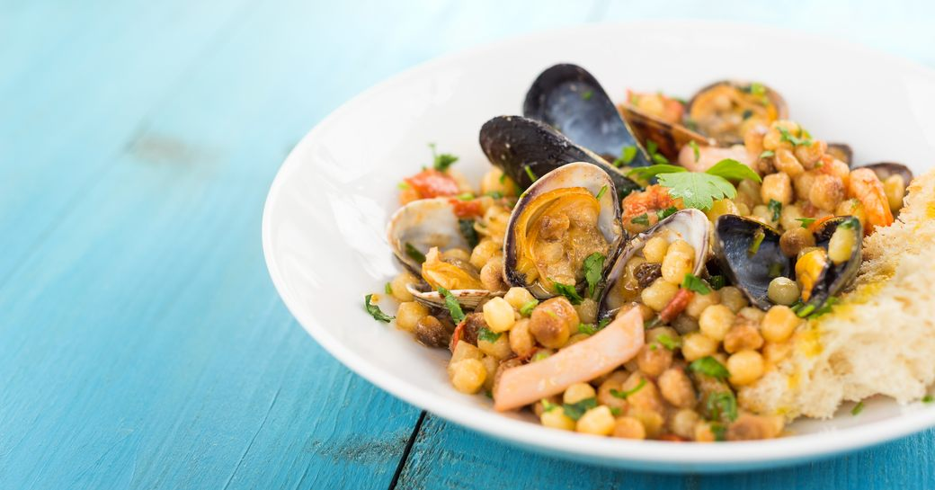 A white dish containing traditional fregula pasta from Sardinia with mussels